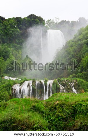 Large waterfall surrounded with green vegetation - stock photo
