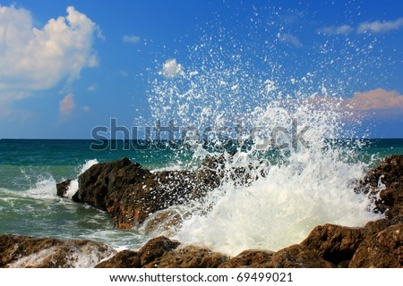 Large wave crash against the rocks during a storm in the tropics - stock photo