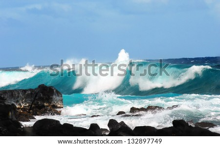 Large wave curls and spills over itself as it crashes against the rocks in Mackenzie State Park on the Big Island of Hawaii.  Windy conditions causes ocean to produce large waves and spray. - stock photo