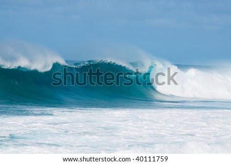 Large waves break off the north shore of oahu hawaii during a great time for surfers surfing. - stock photo