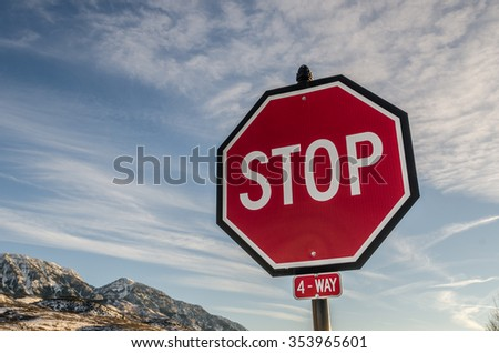 Large 4-way stop sign indicating people were not stopping at the intersection when the sign was normal size - stock photo