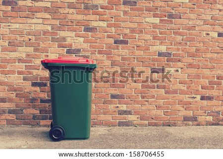 large wheelie bin in front of a brick wall - stock photo