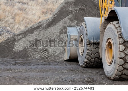 Large wheels and the bucket of a construction loader up against a pile of gravel at a job site.