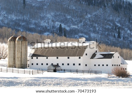 Large white barn in the mountains near Park City, Utah during winter. - stock photo