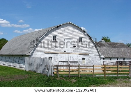 large white barn rounded roof and fence - stock photo