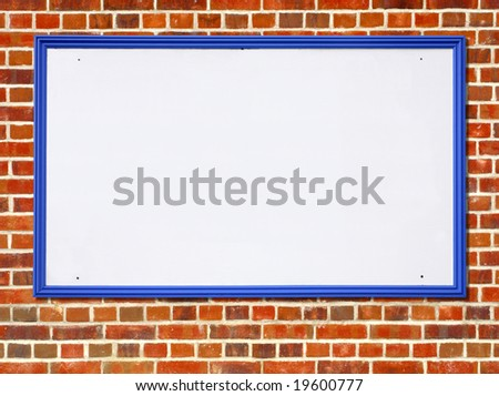 Large white blank billboard sign with a blue wooden frame on a red brick wall. - stock photo