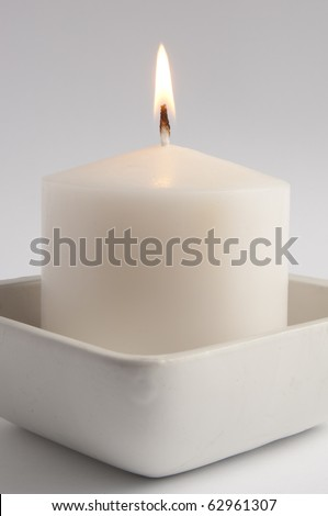 Large white candle in a square tray close up - stock photo