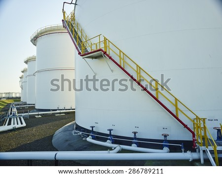 large white fuel containers against blue sky