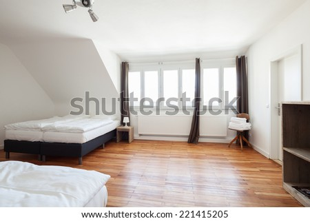 Large white painted bedroom interior with a wooden parquet floor two double beds and a shelving units in minimalist style - stock photo