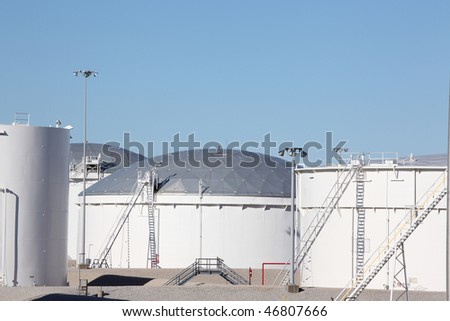 Large white petrochemical storage tanks with domed roofs at a manufacturing plant showing access ladders stairs and walkways and piping - stock photo