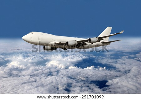 Large white plane without landing gear flying above the clouds - stock photo