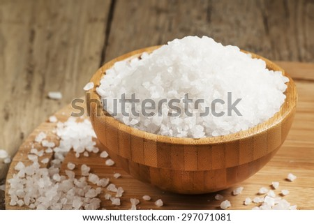 Large white sea salt in a wooden bowl, selective focus