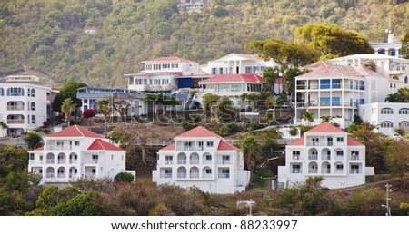 Large white vacation homes on a tropical hillside with red tile roofs - stock photo