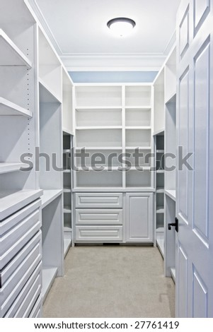 large white walk-in closet with shelves - stock photo