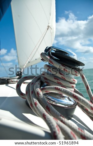 large winch with line wrapped around and set sail in background - stock photo