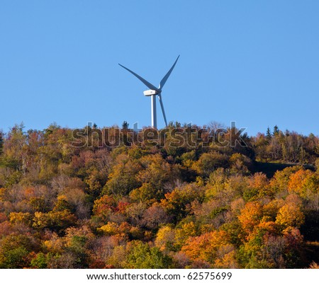 Large wind generator on hilltop above autumn trees - stock photo