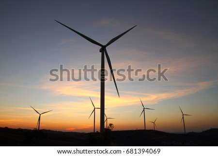 Large wind tubine on big hill at sunset