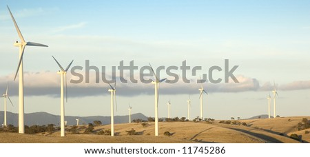 Large wind turbines line up along the hilltop as part of an energy producing windfarm. - stock photo