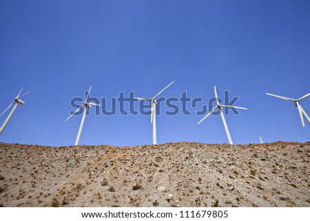 Large windmills on top of a hill in California's mojave desert.
