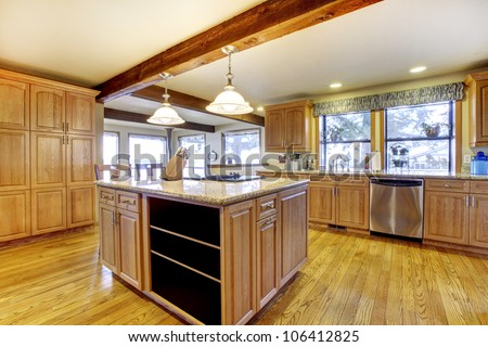 Large wood kitchen with hardwood and wood beam.