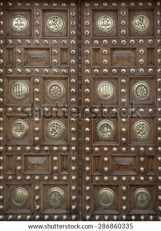 Large wooden doors decorated with metal rivets and minting