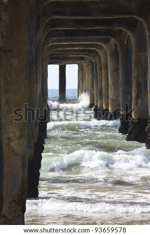 large wooden pier with waves crashing through and under it - stock photo