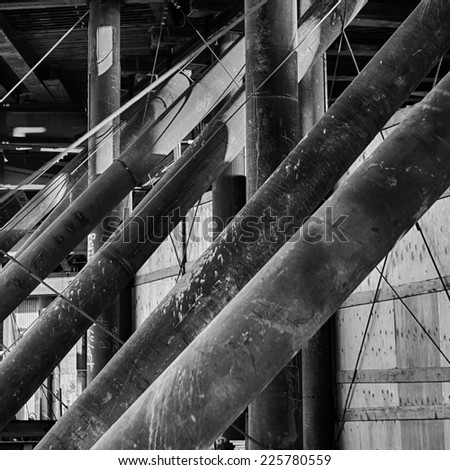 Large wooden poles leaning at an extreme angle. - stock photo