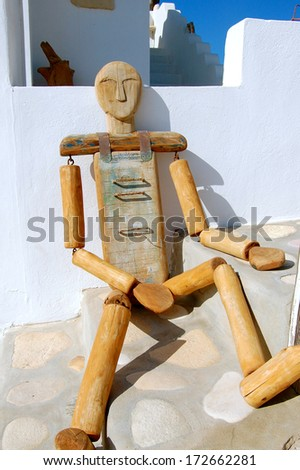Large Wooden Puppet against a wall in a street on Santorini, Greece - stock photo