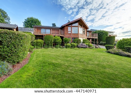 Large wooden trim house with walkway, garage and lots of grass.  - stock photo