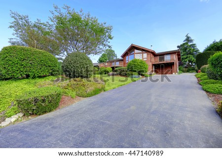Large wooden trim house with walkway, garage and lots of grass. Water view - stock photo