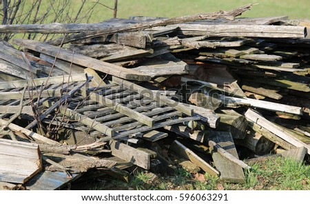 large woodshed with many pieces of wood and other wooden materials in a farm outdoor storage