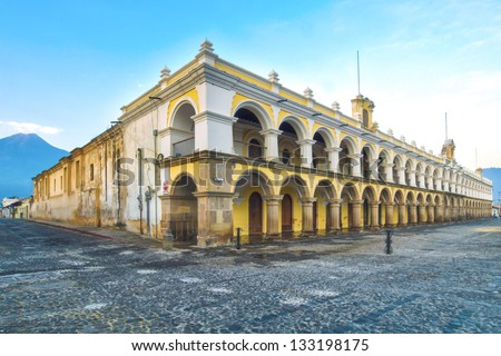Large yellow and white Baroque style building in Antigua, guatemala.  Located in the main square of Antigua's old town. - stock photo