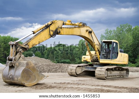 Large Yellow Back Hoe at Construction site.  Storm brewing. - stock photo