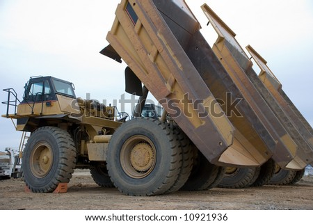 Large yellow dump trucks lined up with beds elevated - stock photo