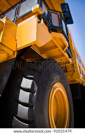 Large yellow truck used in modern Gold Mine in Kalgoorlie, Western Australia. Truck transports gold ore from the Super Pit, Open cast mine. - stock photo