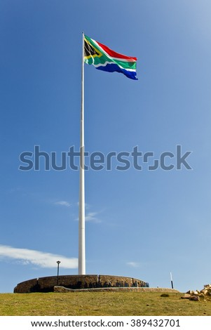 largest South African flag waving in the wind in the afternoon sunlight  - stock photo