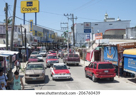 LAS CHOAPAS, MEXICO - JULY 17, 2014: Vehicle and pedestrian traffic flows on even a hot sunny day in downtown Las Choapas, Veracruz. - stock photo