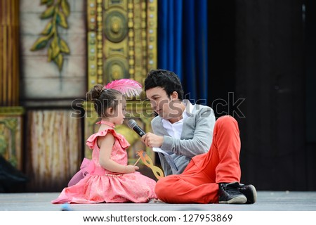 LAS PALMAS, SPAIN - FEBRUARY 10: Unidentified girl (l) and host Baby Solano (r) from Canary Islands, onstage during Children's Costume and Murgas, on February 10, 2013 in Las Palmas, Spain - stock photo
