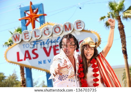 Las Vegas Elvis impersonator having fun cheering by Welcome to Fabulous Las Vegas sign. Funny happy joyful image with Elvis and smiling happy beautiful girl wearing cowboy hat on the Strip - stock photo
