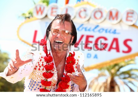 Las Vegas Elvis impersonator laughing having fun in front of Welcome to Fabulous Las Vegas sign. - stock photo