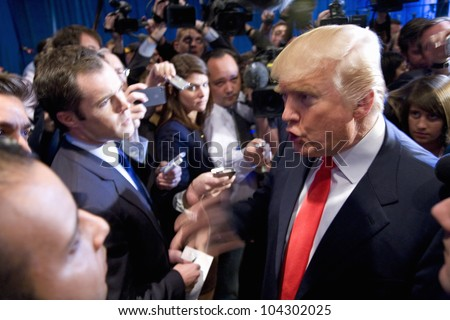 LAS VEGAS - FEB 2: Donald Trump (C) speaks with the media at his hotel on February 2, 2012 in Las Vegas, Nevada. Trump is endorsing Romney for president. - stock photo