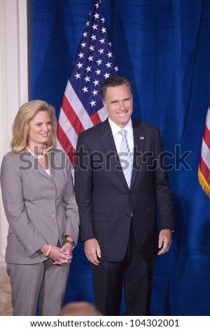 LAS VEGAS - FEB 2: Mitt Romney smiles as he stands with his wife, Ann Romney, while Donald Trump (off camera) endorses him for president at the Trump Hotel on February 2, 2012 in Las Vegas, Nevada. - stock photo