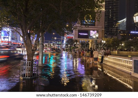 LAS VEGAS - JULY 19,  - Vegas Strip on July 19, 2013 in Las Vegas. Tourists try to make their way down the strip where flood waters make it impossible to determine street from sidewalk.