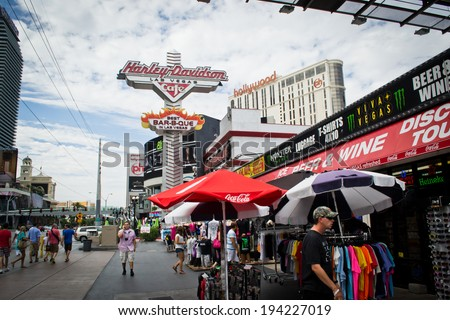 LAS VEGAS,NEVADA,USA - AUGUST, 2 2012: people are walking and shopping along the famous strip of Las Vegas.In this picture you see the Harley Davidson cafe and souvenir shops. - stock photo