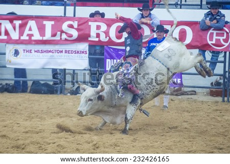 LAS VEGAS - NOV 05 : Cowboy Participating in a Bull riding Competition at the Indian national finals rodeo held in Las Vegas , Nevada on November 05 , 2014  - stock photo