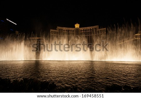 LAS VEGAS, NV -  JUNE 12, 2013:  Las Vegas Bellagio Hotel Casino featured with its famous fountain show at night on June 12, 2013 in Las Vegas, Nevada. Multiple water shows take place every day.  - stock photo