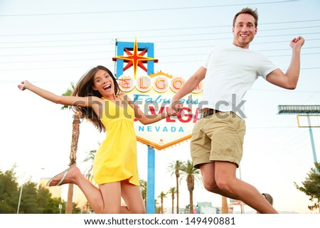 Las Vegas Sign. Happy couple jumping. People having fun in front of Welcome to Fabulous Las Vegas sign. Beautiful young couple on the Strip excited during travel holidays vacation, Nevada, USA. - stock photo