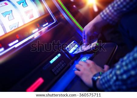 Las Vegas Slot Gambling Addiction. Men Playing Traditional Slot Machine. - stock photo