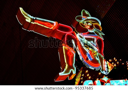 LAS VEGAS, US - OCTOBER 13: Cowgirl neon sign on October 13, 2011 in Las Vegas, US. The iconic sign of Glitter Gulch is placed in 20 East Fremont Street, in Downtown Las Vegas - stock photo