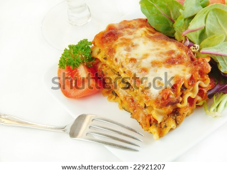 Lasagna and salad on a white plate with a fork. - stock photo